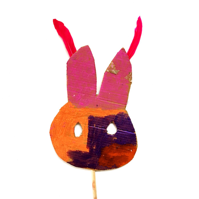 A child made bunny mask with feathers