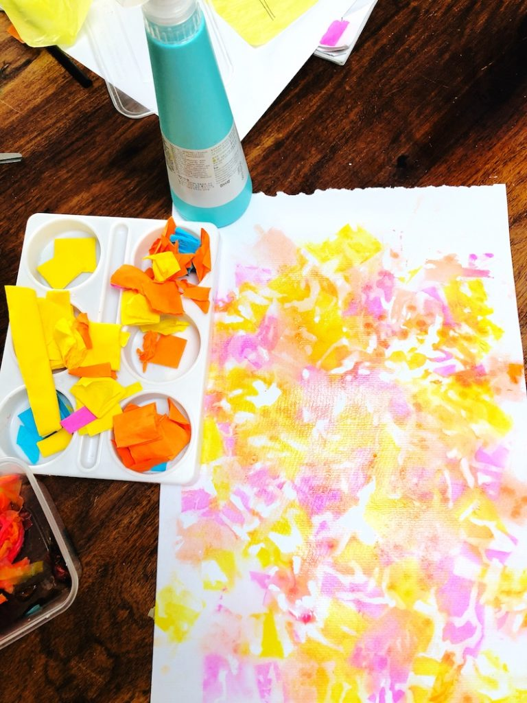 A colourful child's painting with yellow, orange and pink made from wet crepe paper for a SPring flower art project.