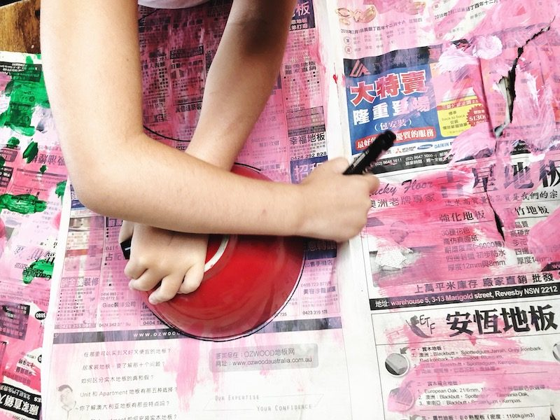 A child's hands traces around a bowl on painted newspaper.