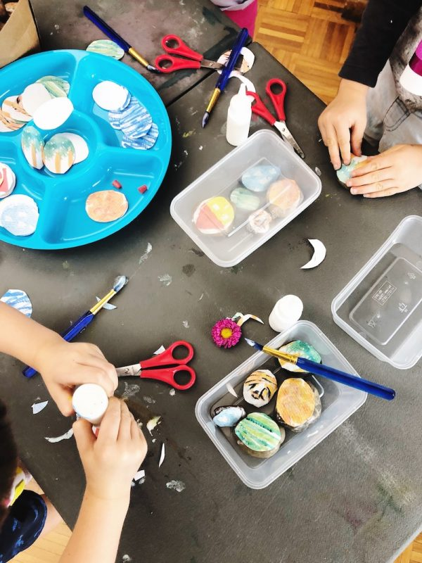 A bird's eye view of a craft table is shown. Childrens' hands are squeezing glue.